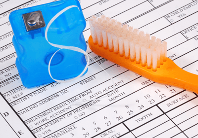 dental insurance paperwork with toothbrush and floss