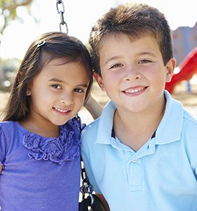 boy and girl smiling on playground