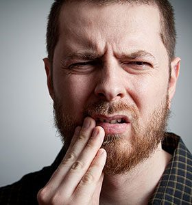 man holding lip in pain