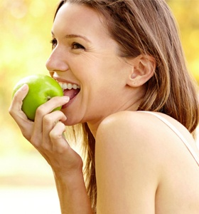 A woman enjoying an apple.