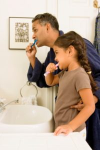 Father and daughter work on the effective at-home dental health routine recommended by the family dentist keller trusts