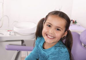 smiling little girl seated in the dentist's chair