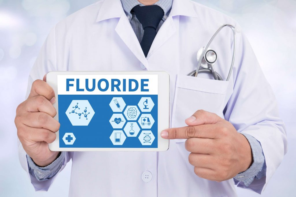 "A dentist holding a sign that reads, ""Fluoride"""