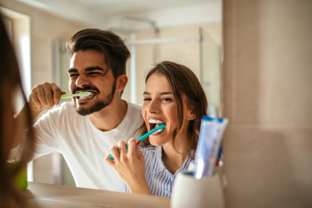 Man and woman brushing their teeth with tips from a dentist