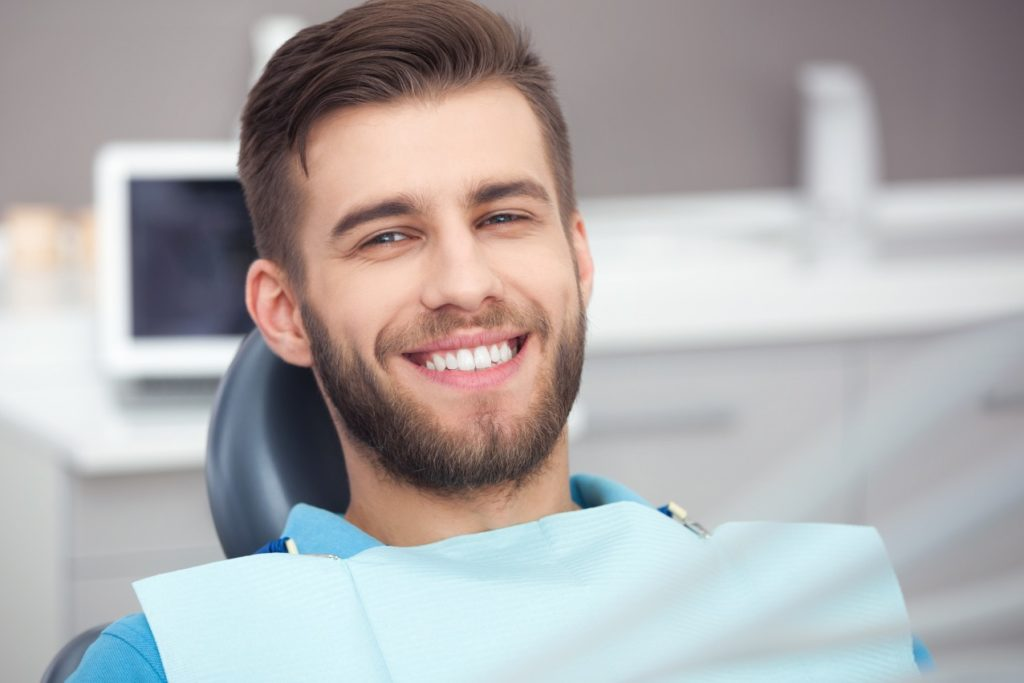 Smiling man in a blue shirt at the dentist