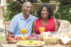 couple eating with dentures at a backyard get-together